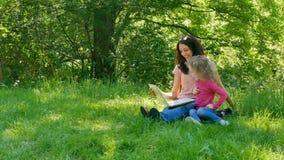 Mooi zit Weinig Dochter met Haar Jonge Moeder op het Groene Gras in het Stadspark met Witte Laptop, het Kijken stock footage