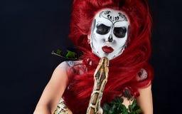 Mooi zombiemeisje met tekeningsgezicht die rotshaak omhelzen stock foto