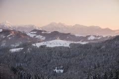 Mooi zonsopganglandschap van Heilige Thomas Church in Slovenië op heuveltop op de winter en Triglav-de bergachtergrond royalty-vrije stock foto's
