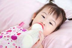 Mooi zuigt weinig Aziatisch meisje die en omhoog melk liggen Stock Afbeelding