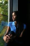 Mooi zwart meisje dat in venster wordt weerspiegeld Stock Foto's