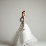 Mooie aantrekkelijke bruid in huwelijkskleding met lange volledige rok, witte achtergrond, dans en glimlach Stock Foto's