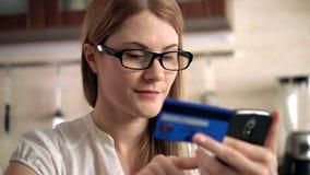 Mooie aantrekkelijke jonge vrouw die in glazen online met creditcard op smartphone kopen Keuken stock video