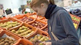 Mooie aantrekkelijke jonge vrouw die kiwienvruchten in supermarkt uitkiezen Gezond het Eten Concept stock videobeelden
