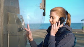 Mooie aantrekkelijke jonge vrouw die met vriend van telefooncel spreken Dijkzonsondergang stock video
