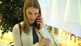 Mooie aantrekkelijke jonge vrouw die op haar smartphone in een wandelgalerij spreken Het winkelen en vrije tijd 00361 stock footage