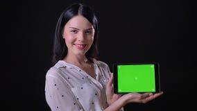 Mooie aantrekkelijke jonge vrouw die die tablet met chromakey en glimlachen tonen, op zwarte achtergrond wordt geïsoleerd stock video