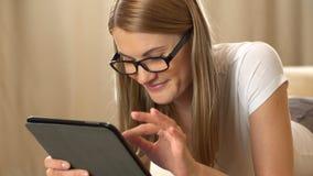 Mooie aantrekkelijke jonge vrouw in een witte t-shirt en zwarte glazen met een tabletcomputer die op een bank liggen browsing stock video