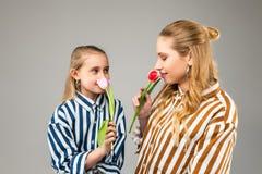 Mooie aantrekkelijke meisjes met lichte haar ruikende geur van eerste de lentetulpen royalty-vrije stock afbeelding