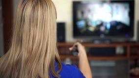 Mooie aantrekkelijke vrouwenzitting op bank en het letten op TV Omschakelingskanalen met afstandsbediening stock video