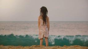 Mooie achterdiemening van weinig jaar 6-8 oud meisje wordt geschoten die op grote golven op tropisch exotisch oceaanstrand in Sri stock footage