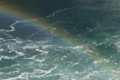 Mooie achtergrond met het water die dichtbij Niagara-dalingen met een regenboog verbazen Royalty-vrije Stock Foto