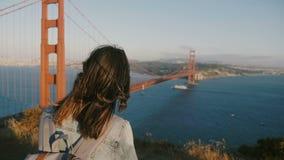 Mooie achtermening van jonge toeristenvrouw met rugzak, haar die in de wind blazen die van zonsondergang genieten in Golden gate  stock videobeelden