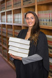 Mooie advocaat die camera in de wetsbibliotheek bekijken Stock Afbeelding