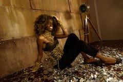 Mooie Afrikaanse Amerikaanse glamour model sexy slaan het met lange benen stelt zitting op vloer bij heldere studio Royalty-vrije Stock Foto's