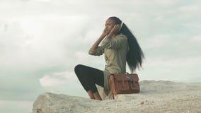 Mooie Afrikaanse Amerikaanse jonge vrouw met smartphone en hoofdtelefoons die aan muziek over blauwe hemel en wolken luisteren stock footage