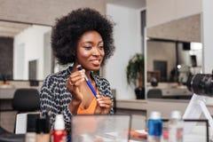 Mooie Afrikaanse Amerikaanse vrouw die met heldere lippenstift geamuseerd kijken stock foto