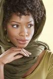 Mooie Afrikaanse Amerikaanse vrouw die weg over gekleurde achtergrond kijken Royalty-vrije Stock Fotografie