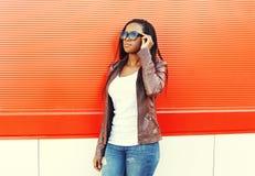 Mooie Afrikaanse vrouw die een leerjasje en zonnebril dragen stock fotografie