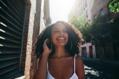 Mooie Afrikaanse vrouw die onderaan de stadsstraat lopen stock foto