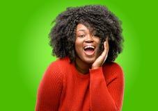 Mooie Afrikaanse vrouw met krullend die haar over groene achtergrond wordt geïsoleerd stock afbeeldingen