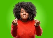Mooie Afrikaanse vrouw met krullend die haar over groene achtergrond wordt geïsoleerd stock afbeelding