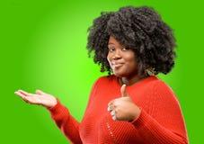 Mooie Afrikaanse vrouw met krullend die haar over groene achtergrond wordt geïsoleerd royalty-vrije stock afbeelding