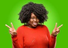 Mooie Afrikaanse vrouw met krullend die haar over groene achtergrond wordt geïsoleerd stock fotografie