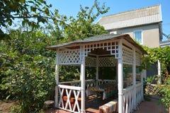 Mooie alkoof, houten as, paviljoen, prieel, de zomerhuis, tuinhuis in de tuin stock fotografie