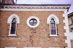 Mooie antieke vensters met friezen op een baksteengebouw Stock Afbeeldingen