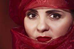 Mooie Arabische vrouw in een rood hoofddeksel Portret van een Arabische vrouw portretclose-up stock afbeelding