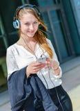 Mooie arbeider die aan muziek vooraan luisteren haar bureau Stock Foto's