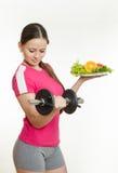 Mooie atleet met een domoor in één hand en een plaat van fruit in een andere Stock Fotografie