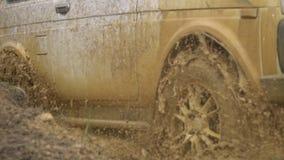 Mooie auto in ruw terrein Krachtig SUV wordt gesleept in een diepe vulklei Extreme drijfvoorwaarden in het platteland