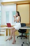 Mooie Aziatische bedrijfsvrouw die zich bij haar bureau in bureau bevindt Stock Afbeelding