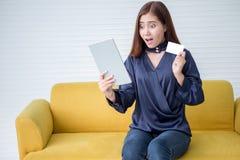 Mooie Aziatische jonge vrouw die creditcard tonen die digitale tabletcomputer houden online winkelend wow glimlachend opgewekt me royalty-vrije stock afbeelding