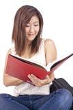Mooie Aziatische jonge vrouw die met rugzak rode book= lezen stock afbeeldingen