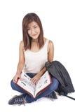 Mooie Aziatische jonge vrouw die met rugzak rood boek lezen stock afbeeldingen
