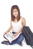 Mooie Aziatische jonge vrouw die met rugzak rood boek lezen stock afbeelding