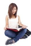 Mooie Aziatische jonge vrouw die met rugzak rood boek lezen stock foto's