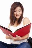 Mooie Aziatische jonge vrouw die met rugzak rood boek lezen stock fotografie