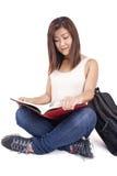 Mooie Aziatische jonge vrouw die met rugzak rood boek lezen royalty-vrije stock afbeeldingen