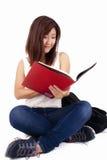 Mooie Aziatische jonge vrouw die met rugzak rood boek lezen royalty-vrije stock foto's