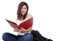 Mooie Aziatische jonge vrouw die met rugzak rood boek lezen royalty-vrije stock fotografie