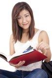 Mooie Aziatische jonge vrouw die met rugzak rood boek lezen royalty-vrije stock afbeelding