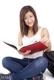 Mooie Aziatische jonge vrouw die met rugzak rood boek lezen stock foto