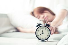 Mooie Aziatische jonge vrouwendraai van wekker in ochtend, kielzog omhoog voor slaap met wekker royalty-vrije stock afbeeldingen