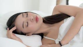 Mooie Aziatische jonge vrouwenslaap die in bed met hoofd op hoofdkussen comfortabele en gelukkige bewegende panning camera liggen stock video