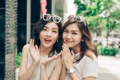 Mooie Aziatische meisjes die met het winkelen zakken op straat bij Th lopen Royalty-vrije Stock Afbeeldingen