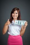 Mooie Aziatische meisjesduimen omhoog met een 100 dollarrekening Stock Afbeelding